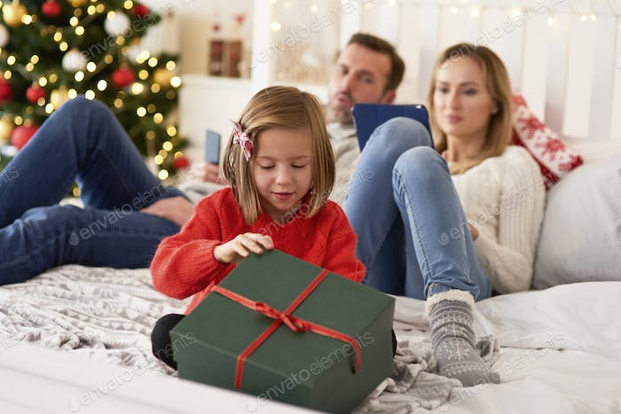 Child opening  gift and parents with technology in the background