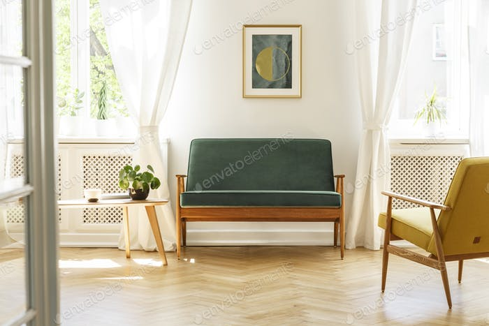 Green sofa with dark, wooden frame and a comfy yellow armchair i