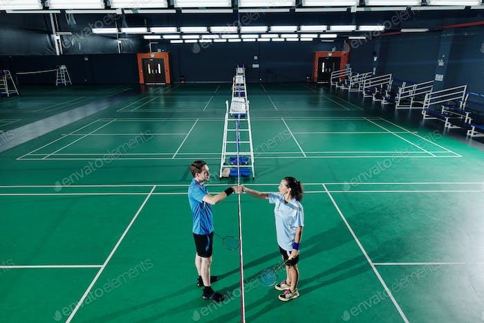 Badminton players training in gymnasium