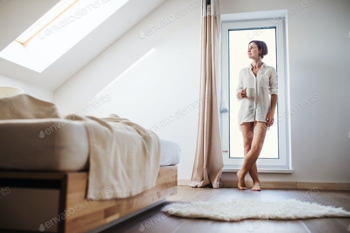 A young woman with night shirt standing by the window in the morning.