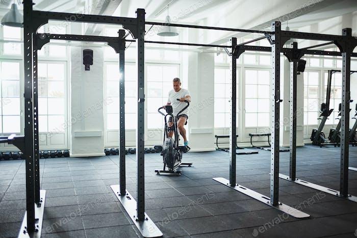Reifen Mann arbeiten aus auf ein Gesundheitsclub stationäre Fahrrad