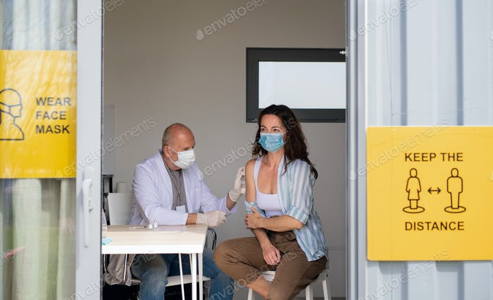 A young woman indoors getting vaccinated, coronavirus concept