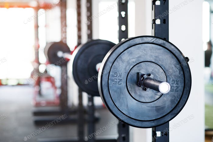 Metal heavy barbell in holder in modern gym.