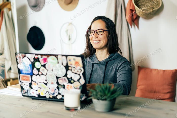 Happy cheerful  woman works on a stylish laptop decorated with pictures