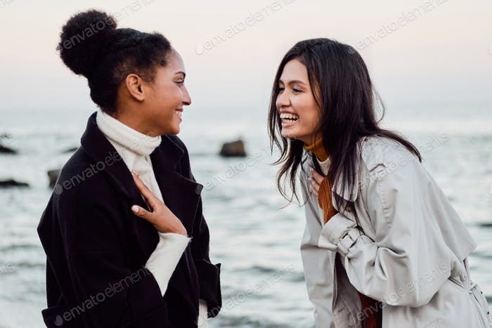 Two cheerful casual girls happily talking walking together by the sea