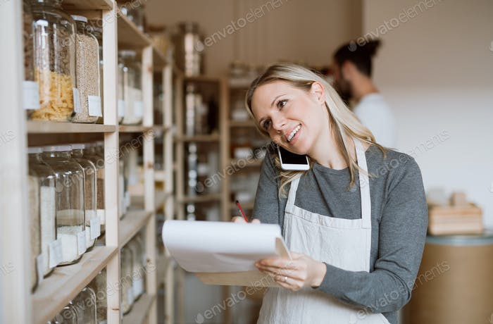 A female shop assistant with smartphone working in a zero-waste shop.