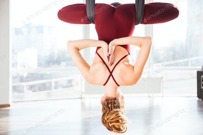 Attractive woman doing pose of antigravity yoga
