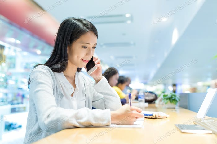 Woman writing on the note and talk to cellphone in coffee shop