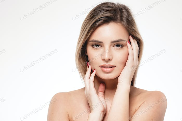 Beautiful woman is touching her face by fingers. face portrait close up studio on white blonde .