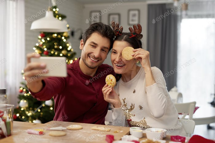 Playful couple making a selfie at Christmas