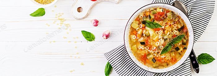 Minestrone, italian vegetable soup with pasta on white table. Ve