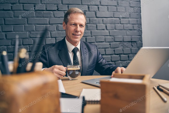 Cheerful male person going to drink aroma coffee