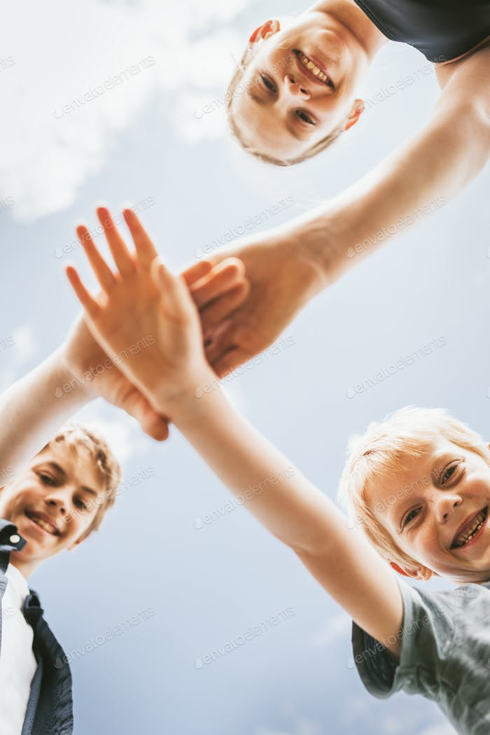 Teamwork background, kids stacking hands in the middle, family photo