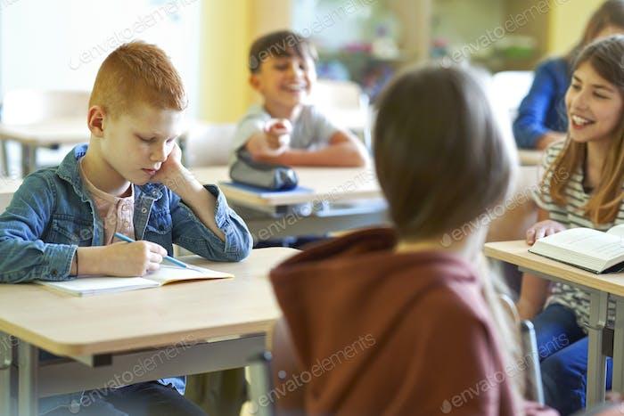 Sad schoolboy writing in note book