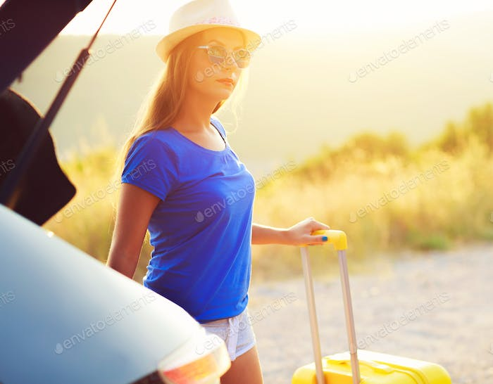 Woman with a yellow suitcase standing near the trunk of a car pa