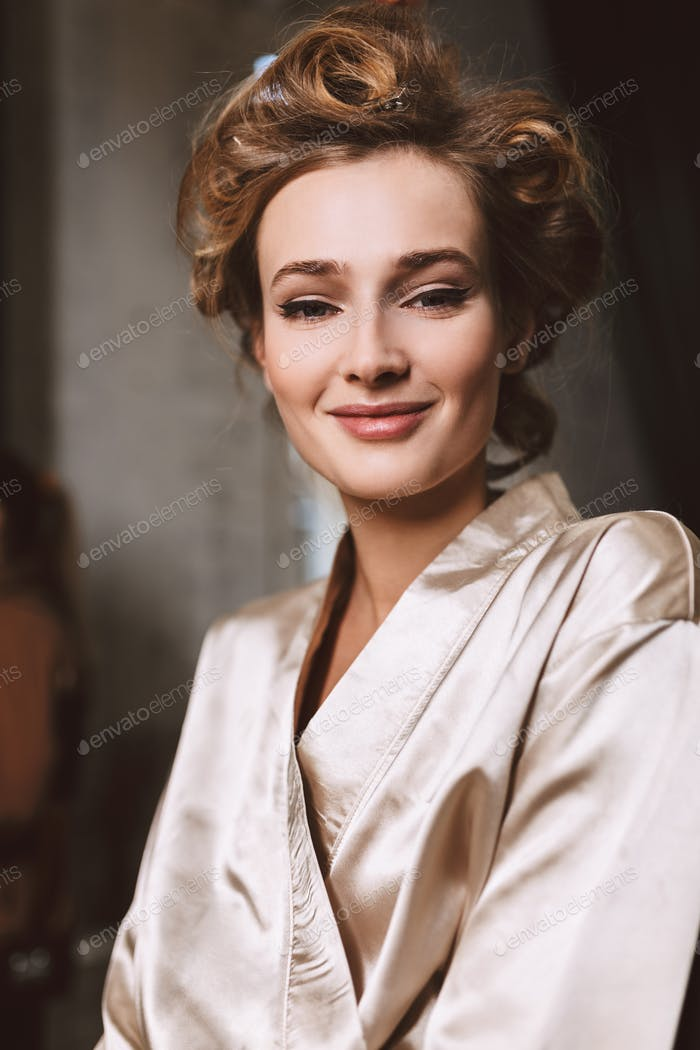 Young gorgeous smiling woman with wavy hairstyle in silk robe ha