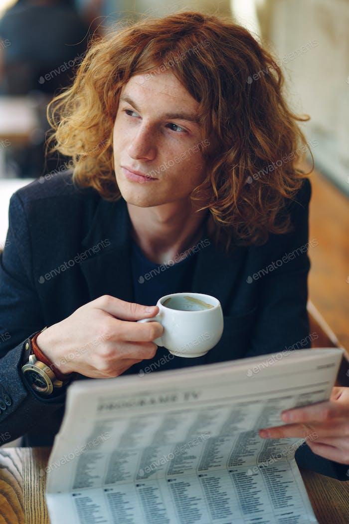 Hombre hipster bebiendo café mientras piensa en el Futuro