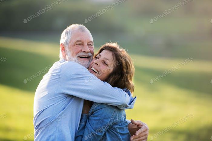 Senior couple hugging outside in spring nature.