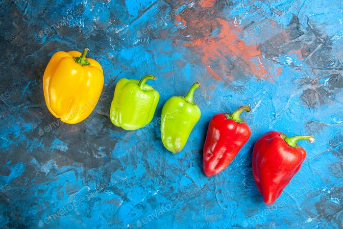 top view fresh bell-peppers different colored on blue background salad vegetable food color