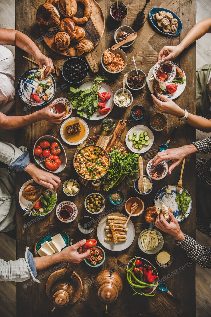 Flat-lay of Turkish breakfast and peoples hands with food