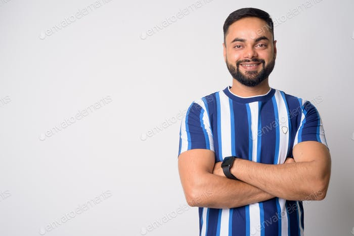 Portrait of happy young bearded Indian man smiling with arms crossed