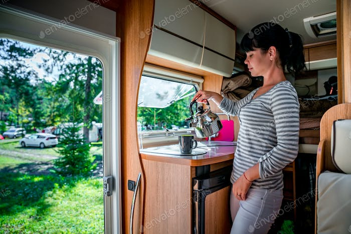 Woman cooking in camper, motorhome interior RV