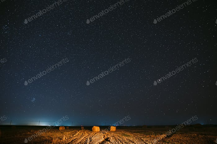 Night Starry Sky Above Haystacks In Summer Agricultural Field. Night Stars Above Rural Landscape