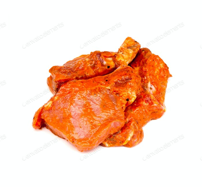 The pieces of meat in the marinade on a white