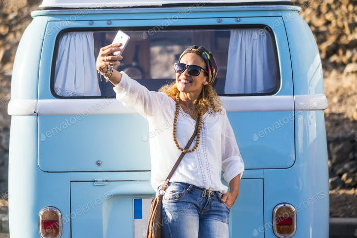 Cheerful caucasian 40 years old woman smile and take a selfie picture with phone cell