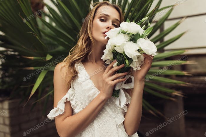 Young attractive woman in white dress holding little bridal bouq