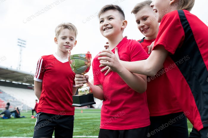 Junior Football Team Holding Cup