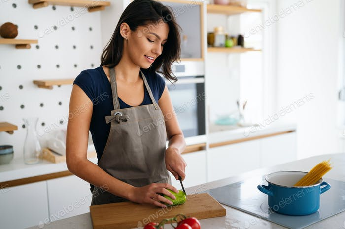 Beautiful young woman cooking at home. Healthy food, people concept