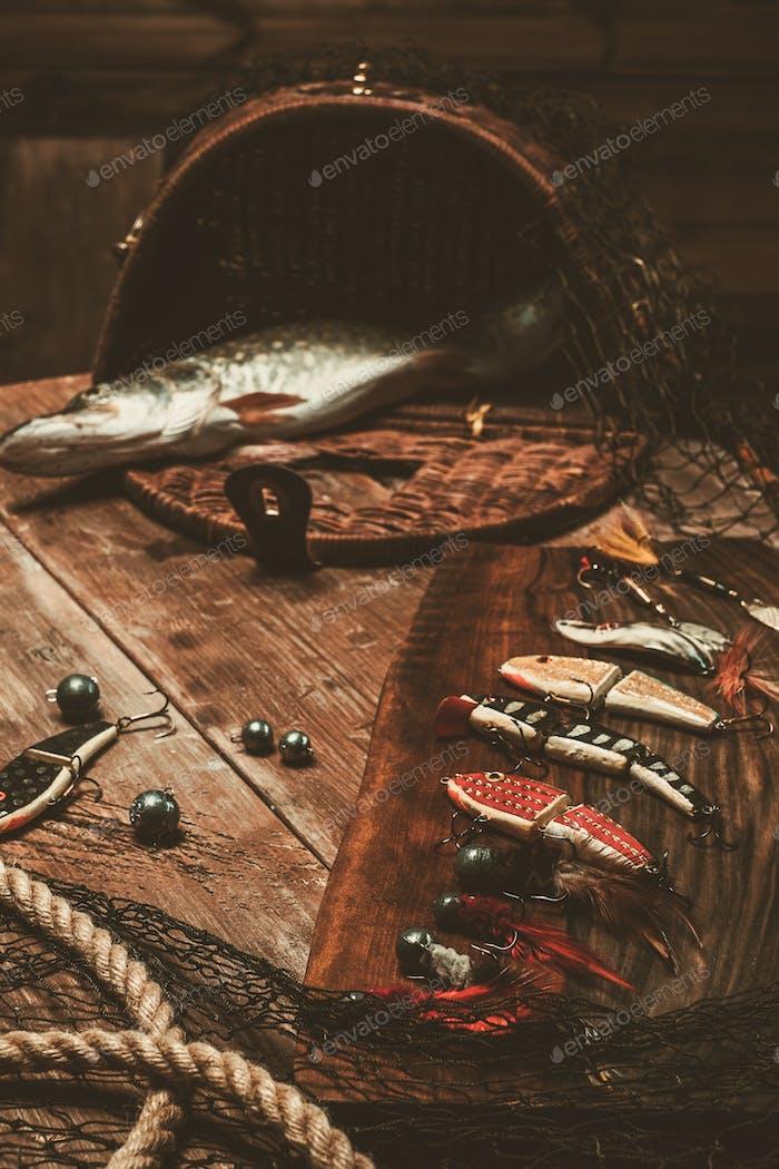 Herramientas de pesca y lucio fresco en una mesa de De madera
