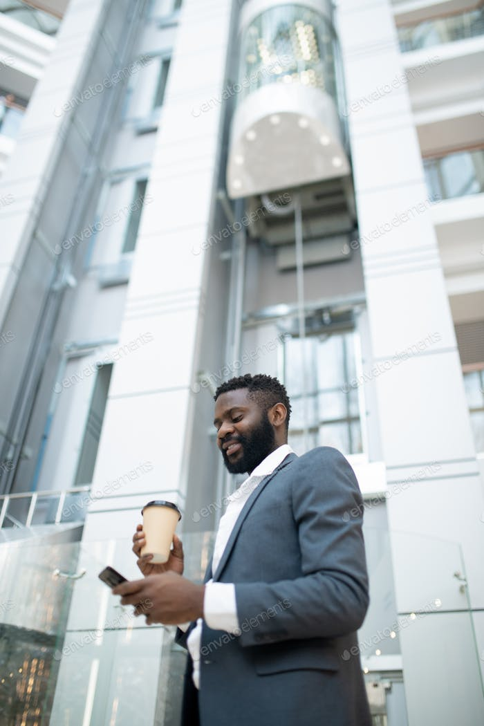 Smiling young Black businessman checking sms