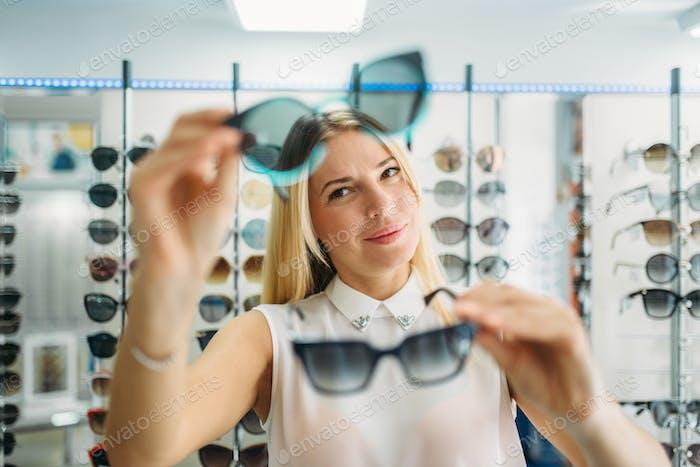 Female buyer chooses sunglasses in optics store
