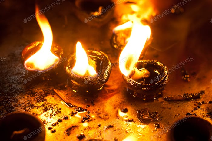 Burning oil lamps at religious temple. India