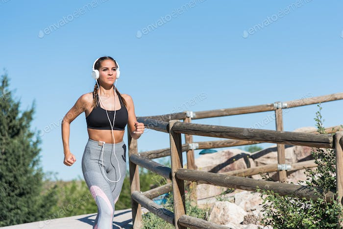 young sports Woman running jogging in a park outdoors listening music