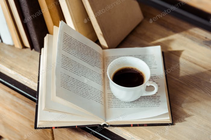 close up of open book with cup of coffee on bookshelf