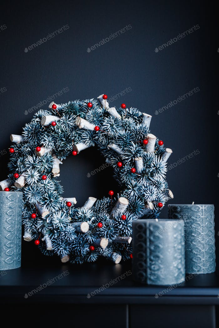 Grey candles and Christmas wreath on a decorative fireplace against black wall