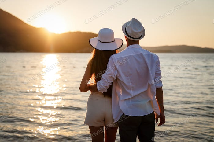 Attractive young couple on the beach, enjoying summer vacation, travel