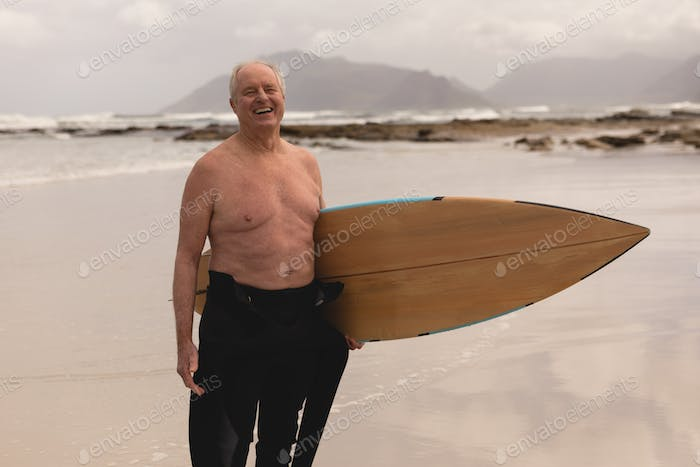 Front view of active senior man standing with surfboard on the beach against mountains background