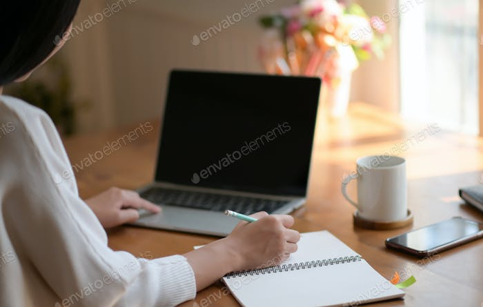 A young woman is using a laptop and writing a report. She works from home.