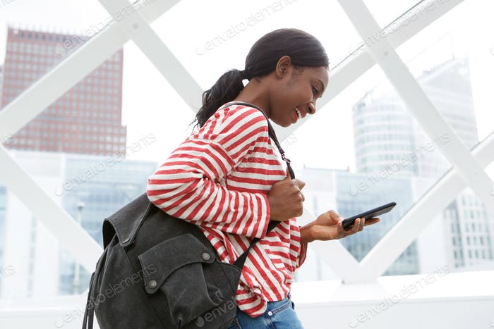 happy african american woman walking and looking at cellphone text message