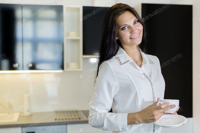 Schöne Frau hält eine Tasse in einer Küche