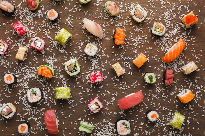 Set of sushi, maki and rolls with sesame on wooden rustic background, top view