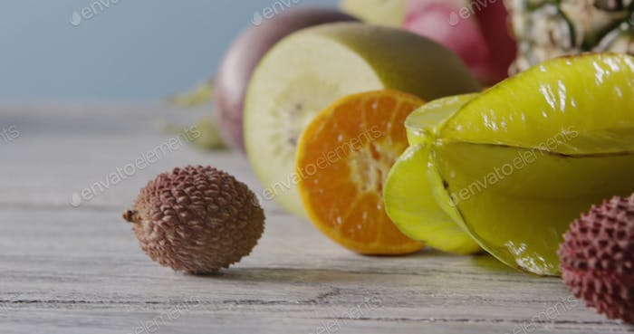 Fresh natural organic exotic fruits on a wooden gray background. Concept of vegetarian diet eating