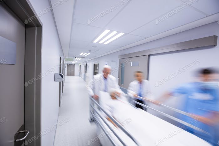 Doctors and nurse pushing emergency stretcher bed in corridor