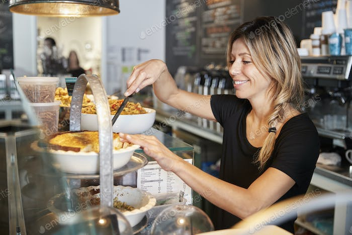 Waitress Behind Counter In Coffee Shop Cutting Slice Of Cake