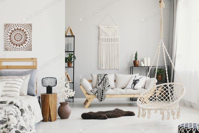 Helles Wohnzimmer Interieur mit Makramee an der Wand, beige Couc