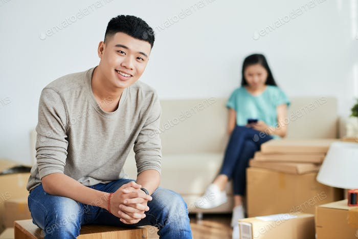 Cheerful Asian man in new apartment